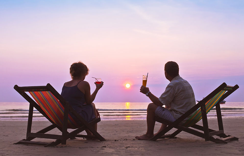 a man and woman sitting on deckchairs at the edge of the ocean watching the sun set over a purple sky