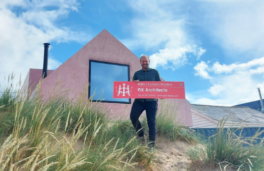 Architect holding a RIBA Site Signboard outside a house