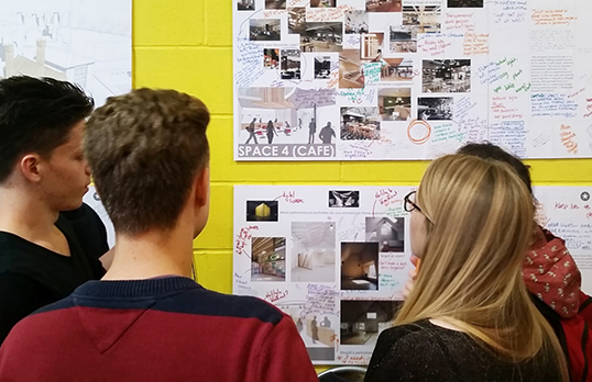 People gather around plans attached to a wall in the Contact Theatre extension project