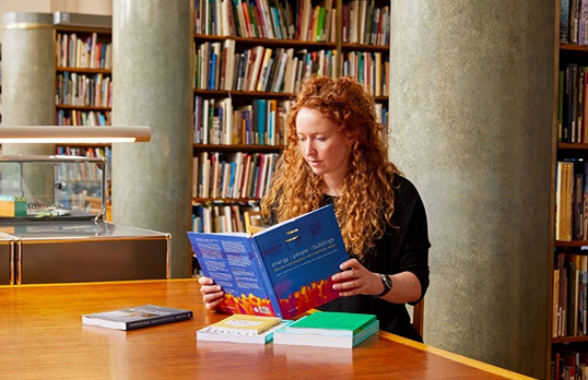 Woman with ginger hair sitting in a library reading a book