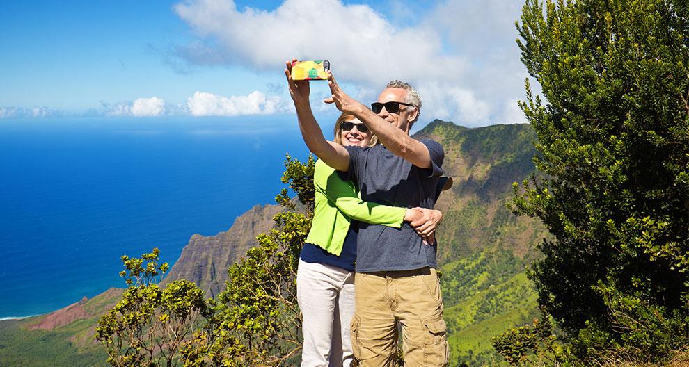 a man and women take a selfie on a mountainside overlooking a deep blue sea