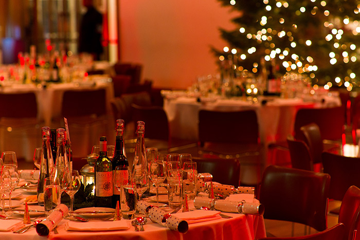 Tables set for Christmas dinner under a warm red glow of light